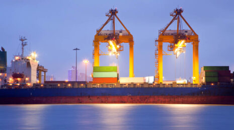Panorama of Container Cargo freight ship with working crane bridge in shipyard at dusk for Logistic Import Export background